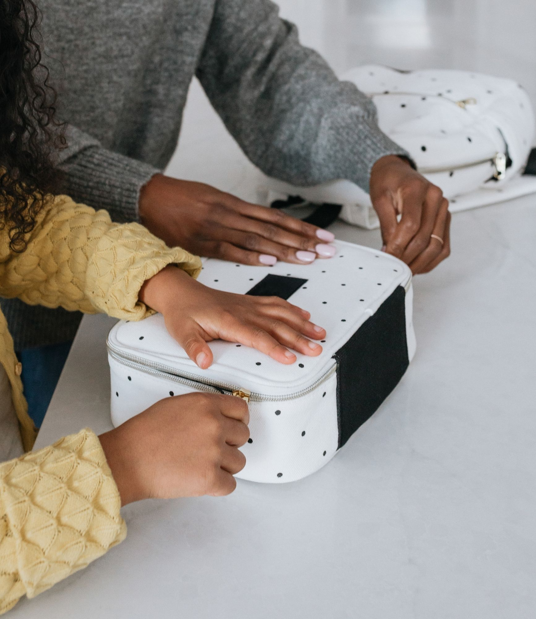 a child and her mother packing up the child's white polka dot lunchbox