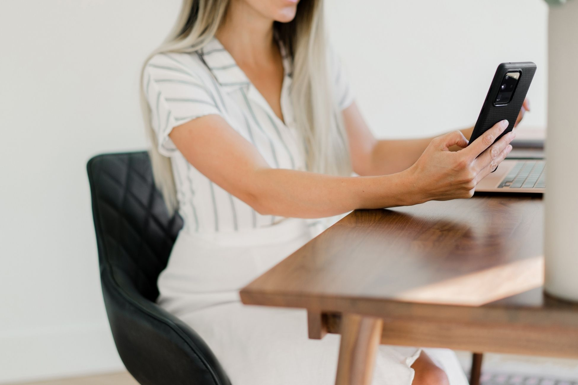 A registered dietitian sharing photos from her cell phone while sitting at a wooden desk