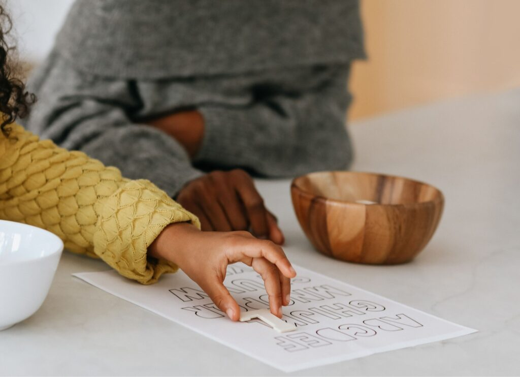 a child in a yellow sweater placing a wooden letter l on an alphabet worksheet