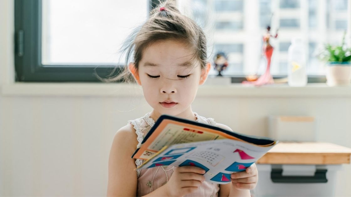 Child reading a book to herself, a healthy food activity for preschoolers