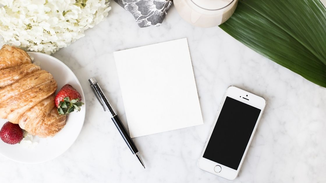 A phone, notepad, pen and croissant on a white background with a green leaf and candle