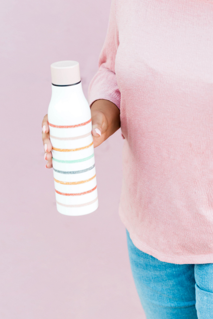 Woman holding pink striped water bottle; a CSSD dietitian can help with hydration for endurance athletes.