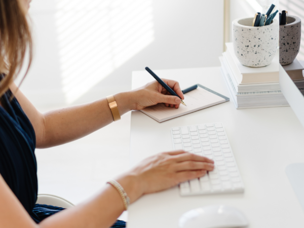 A woman at a white desk writing in a notebook about gentle nutrition
