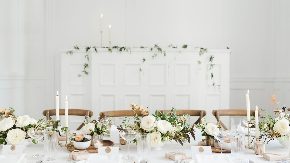 The table is set for a holiday meal with white dishes, candles and many bouquets