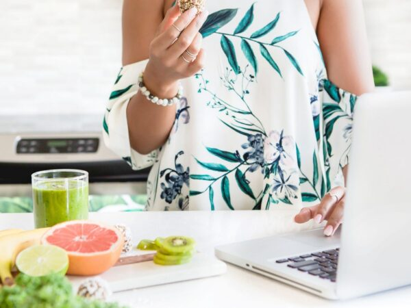 woman standing in kitchen using laptop and eating
