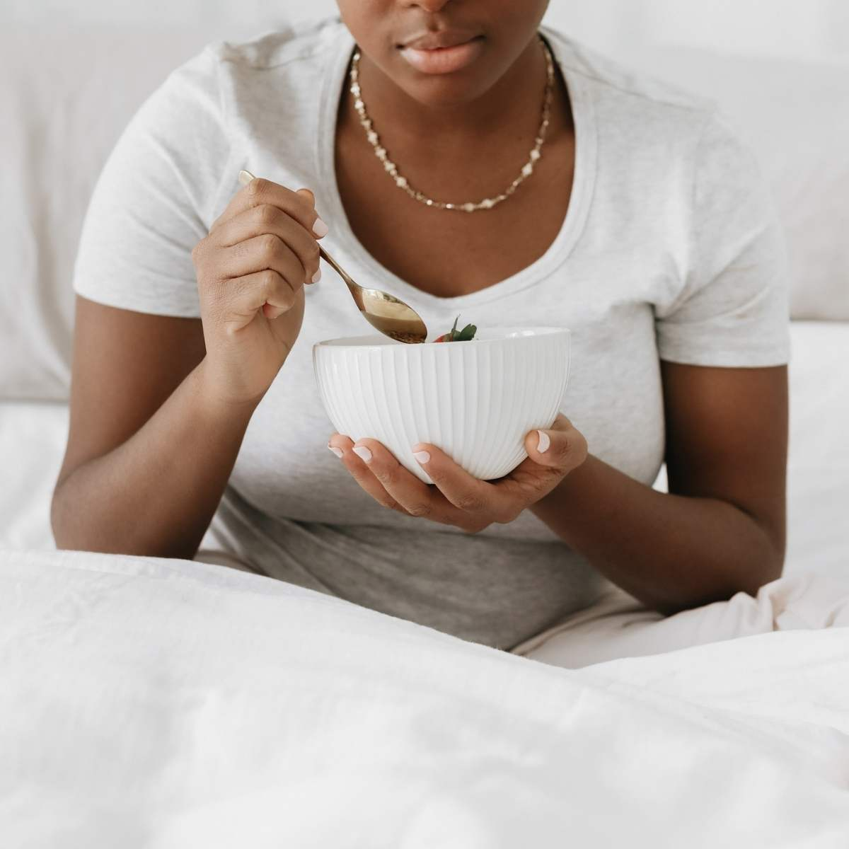 a woman sitting in bed eating breakfast out of a white bowl