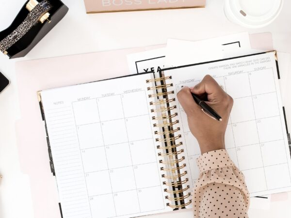woman writing on open monthly calendar
