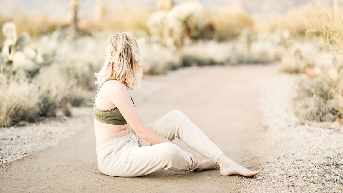 a woman sitting on the ground stretching in a light-filled desert