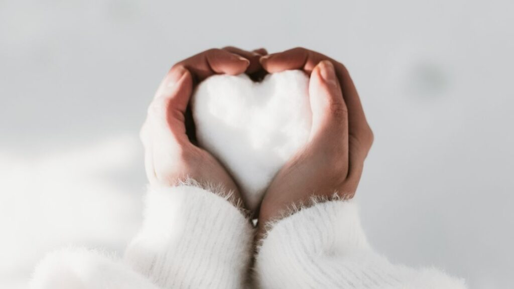 a woman in a white sweater making a heart-shaped snowball with her hands