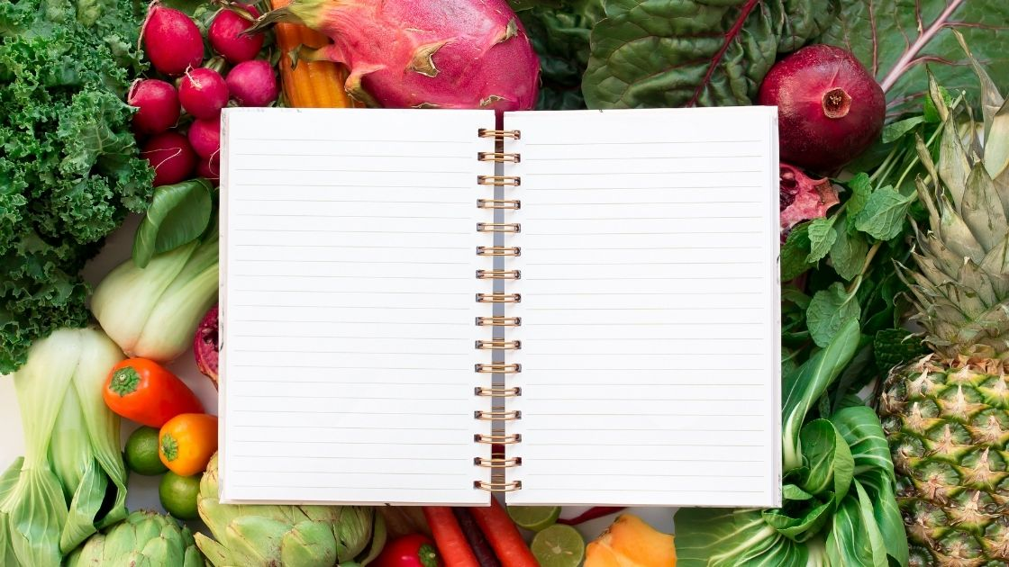An open notebook on top of colorful fruits and vegetables