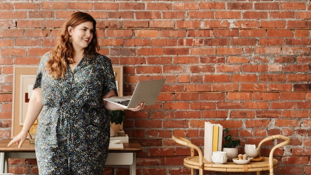 woman holding a laptop in front of a brick wall making a national nutrition month presentation