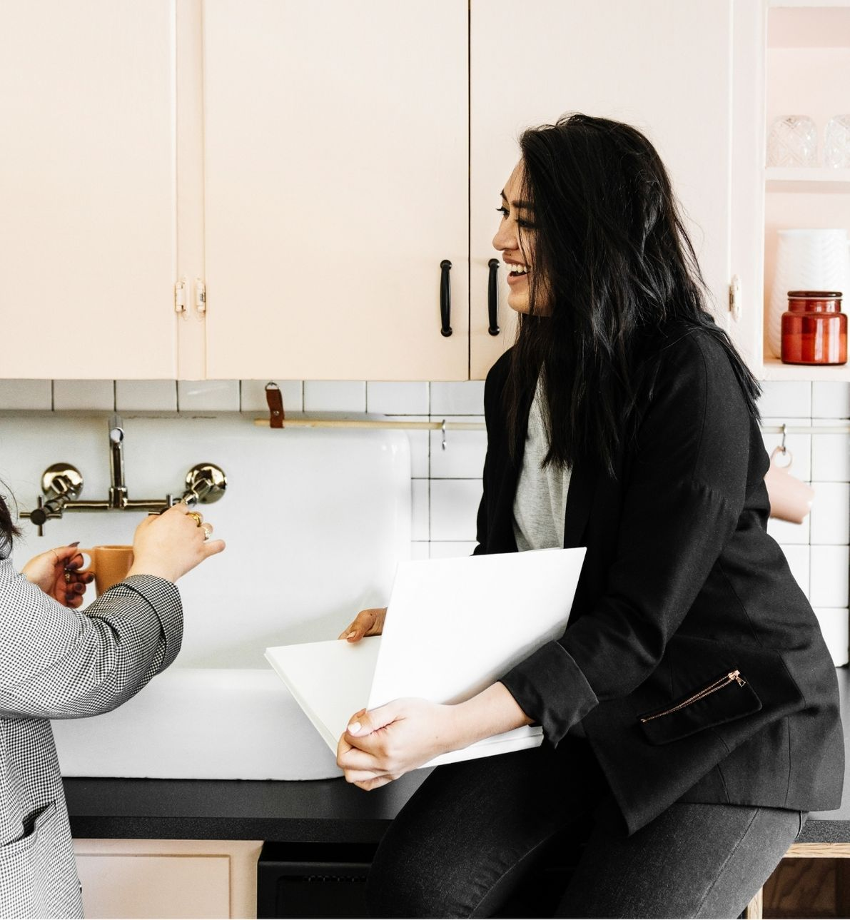 a woman leaning against a counter chatting with another woman fixing a coffee