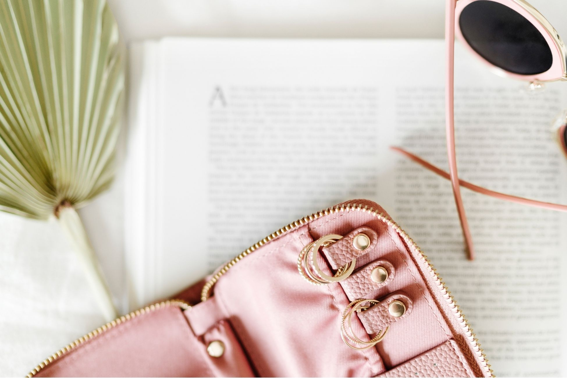 a pink zippered wallet, sun glasses and a journal collected on a table.
