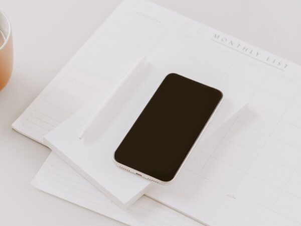 a cell phone on top of a monthly planner on a desk