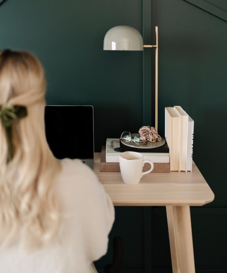 A dietitian intern working on remote project ideas; she's sitting at a desk with a laptop and coffee