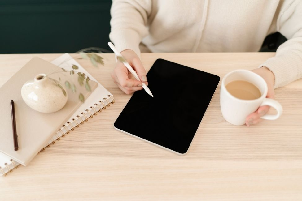 a dietitian writing on a tablet, holding a cup of warm coffee. The table is wooden.