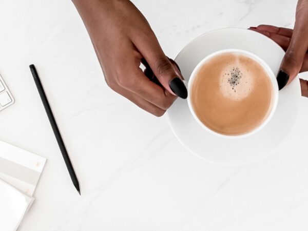 woman at desk holding cup of coffee