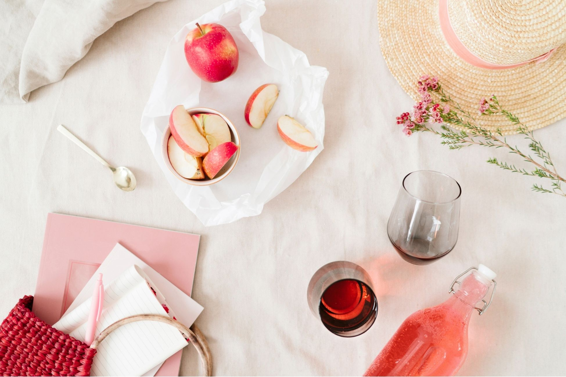 a self-care collection of a journal, fresh apple slices, wine, flowers and a sun hat on a white background.