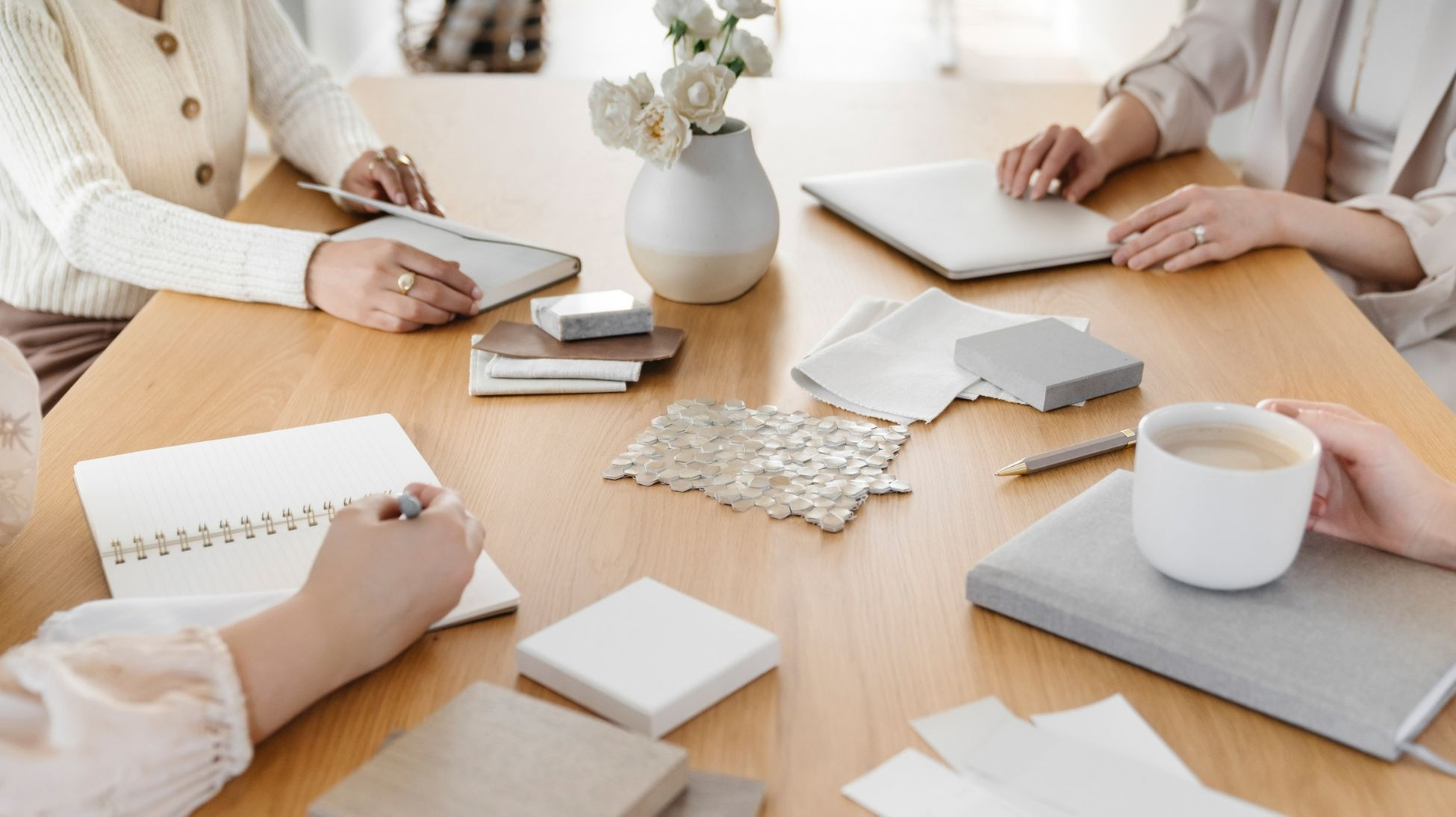 a group of women around a table at a meeting; notebooks at coffee at the ready
