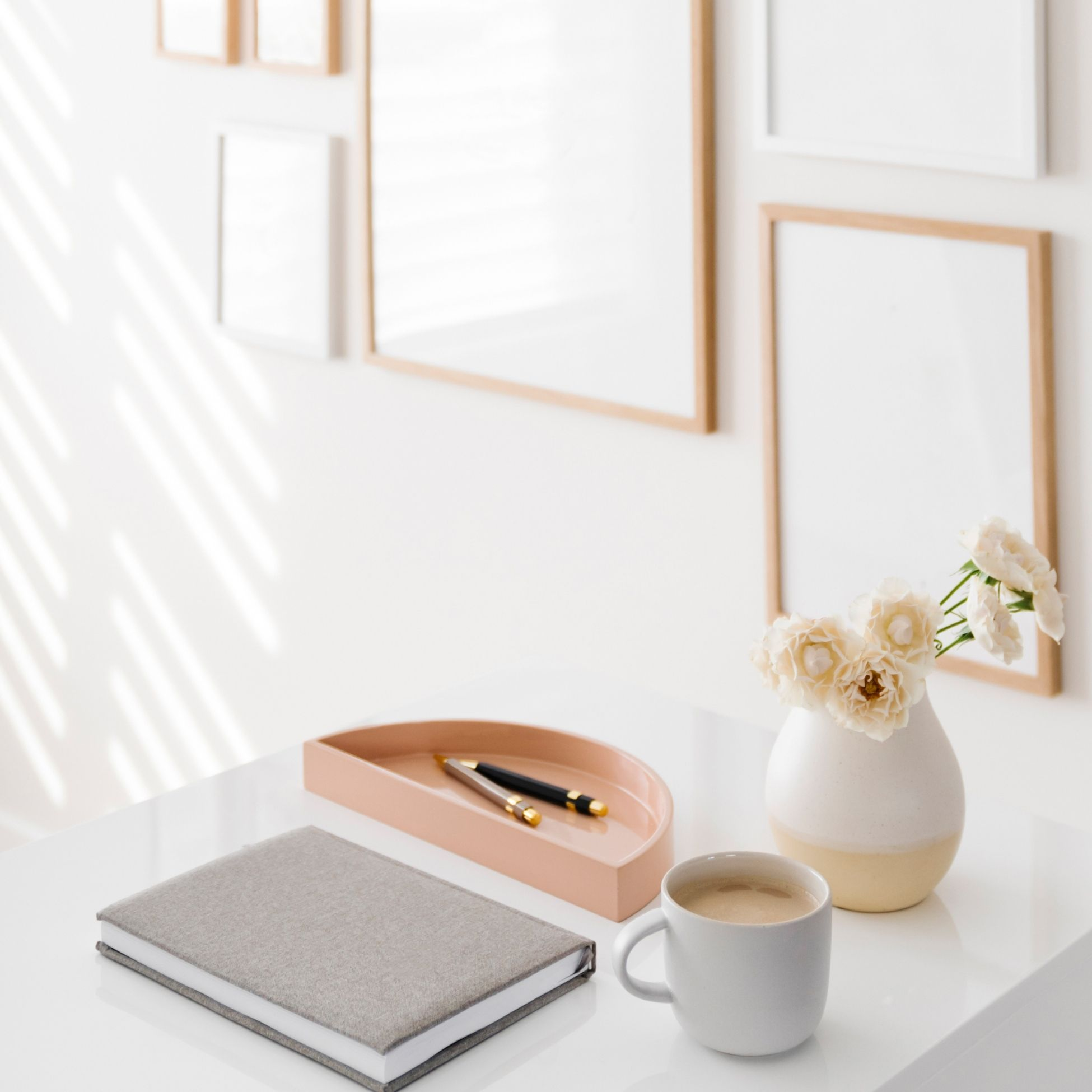 A desk ready to take notes; a notebook and pen are next to a cup of coffee and vase of flowers