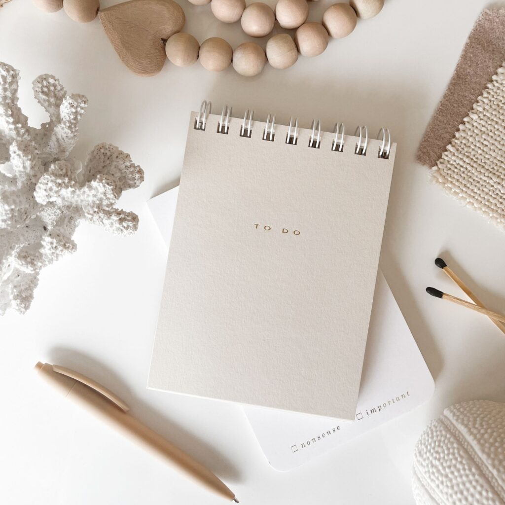 """a white notebook with """"to do"""" written on the cover, next to a gold pen, seashells and a necklace"""