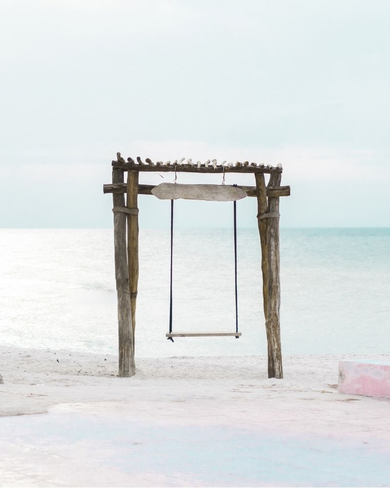 a wooden swing hanging on a frame made from driftwood, on a beach