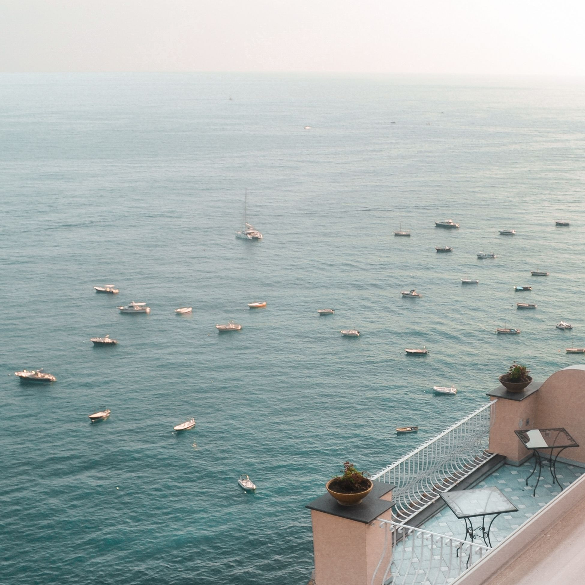 a seaside view from a balcony looking at many small sailboats below