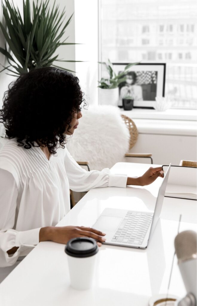 Woman working at her desk with her laptop and notebook