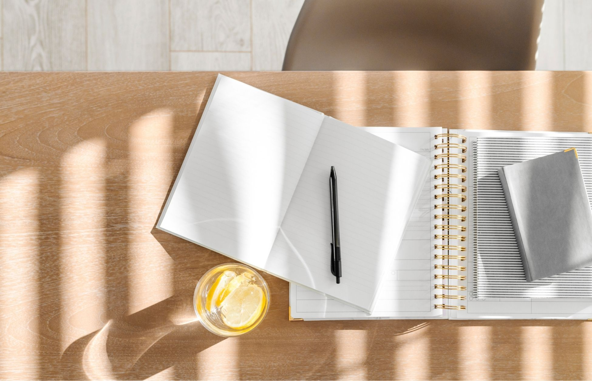 : a sunny desk with open blank notebooks, a pen and a glass of lemon water