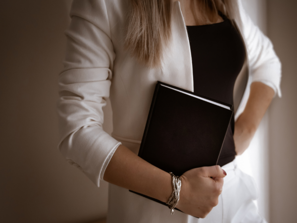 woman holding black notebook